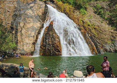 Goa, India - November 16, 2012: An unidentified tourists swimming take photos and enjoying in water of Dudhsagar Waterfall in Goa, India.