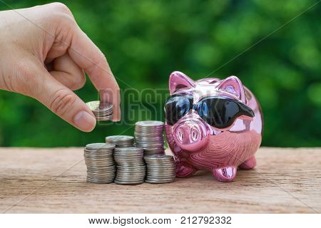 Woman hand holding coins on stack of coins and glossy pink piggy bank as saving or financial wealth concept.