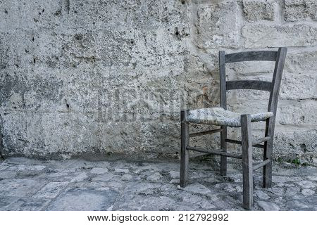 aged old traditional chair in empty stone room in ancient ghost town abandon town Matera south Italy.