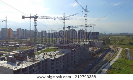 Aerial view on construction building. Construction site workers, aerial, Top View. Overhead view of construction site with large crane. Aerial view of collapsed floor on a building site and builders working 4K