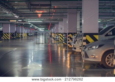 Abstract blurred car parking, garage, interior of underground parking with cars in building of shopping mall. Defocused, for background use