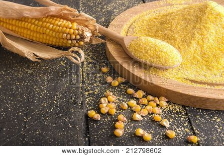 Corn cob and flour spread on table - Food ingredients theme image with a corn cob grains and corn flour on a wooden trencher and spoon on a rustic wooden table.