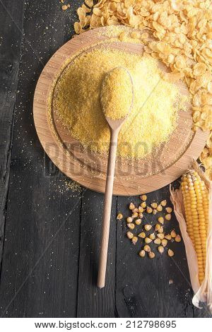 Corn flakes and their key ingredient - Above view with a pile of corn flour on a wooden spoon and trencher surrounded by corn flakes grains and corn cob on a black rustic table.