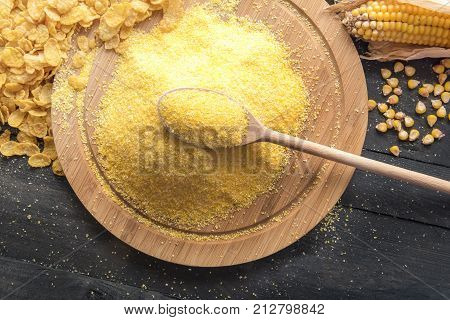 Corn flour and cereal flakes - Rustic image with a wooden spoon full of corn flour on top of a wooden board surrounded by corn flakes grains and corn cob on a black wooden table.