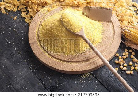 Pile of corn flour with an empty label - Food theme image with corn flour on a round wooden board and a spoon with a blank etiquette surrounded by corn flakes and grains on a rustic black table.