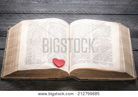 Red heart on an antique book - Open old book with a red little heart on its pages displayed on a black wooden table. Concept for love of reading education or romantic novel.