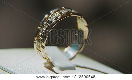 Golden finger ring with yellow precious stone. Ring in gold with sapphires browm, wedding ring - jewelery with diamonds and precious gems black background. Silver or white gold ring with yellow gems and diamonds on black glass background poster