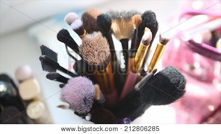 Makeup tools stand at the table. Professional cosmetic devices. Brush and cosmetic and another makeup tools. Top view.