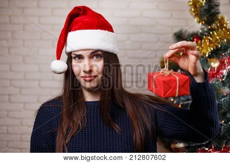 Young Cute Disappointed Woman In Santa Cap Discontented With A Gift. New Year, Christmas, Gift, Surp