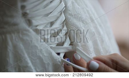 Woman laces up corset on bride's delicate waist. Close-up of woman's fingers lacing up bride's corset on her back. Tender hands of young women button up lace dress on bride's back. Wedding HD