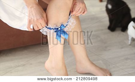Bride wearing wedding garter. The bride wears a garter on the leg. Close-up of young bride putting on white grater. Morning of young beautiful bride. Woman wearing bridal garter. beginning of the wedding day. the bride wears a wedding garter. Wedding HD