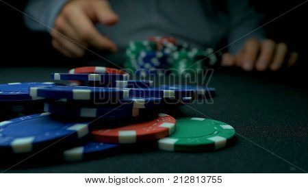 Close-Up of Man Throwing a Poker Chips. Close-up of hand with throwing gambling chips on black background. Poker player increasing his stakes throwing tokens onto the gaming table to meet or beat his opponents wager to stay in the game.
