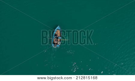 Aerial Boat On The Lake. Aerial View On Two Men In A Boat On A Lake, Rowed To The Shore. Lonely Boat