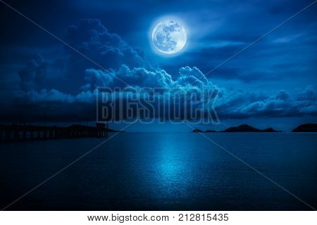 Beautiful landscape view of the sea. Colorful blue sky with clouds and bright full moon on seascape to night. Serenity nature background outdoor at nighttime. The moon taken with my own camera.
