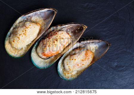 Baked shellfish mussels on dark stone background. Delicious seafood on dark stone background. Delicious seafood poster