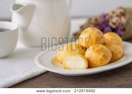 Homemade cream puffs or eclair or choux cream filled with vanilla custard cream on white plate put on wood table with copy space serve with tea in white pot or cup of coffee. Choux cream is French dessert for served with afternoon tea or coffee break.