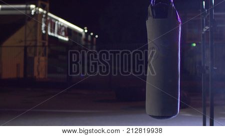 Punching bag in empty street filled with smoke, night. Punching bag hanging in the street at night. Black the punching bag reeling and sways HD poster