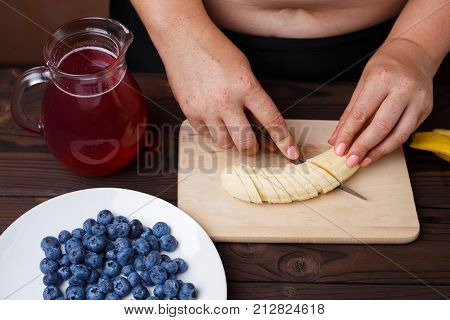 Overweight Fat Woman Slicing A Banana For Fruit Plate. Juicy Tasty Low-calorie Dessert For Weight Lo
