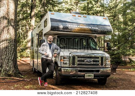 Canada Ontario Algonquin National Park 30.09.2017 - man in front of Parked RV camper car at Lake of two rivers Campground Beautiful natural forest Cruise America