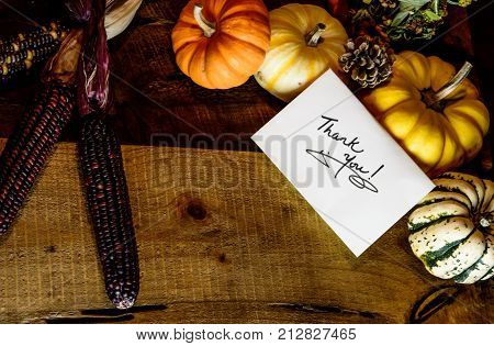 Thanksgiving Thank You Card 2017 in Autumn Harvest Thanksgiving rustic wood decor dinner table with holiday centerpiece and elegant greeting card with holiday gratitude  written words Thank You and Thanksgiving Day symbols Or Giving Tuesday thanks