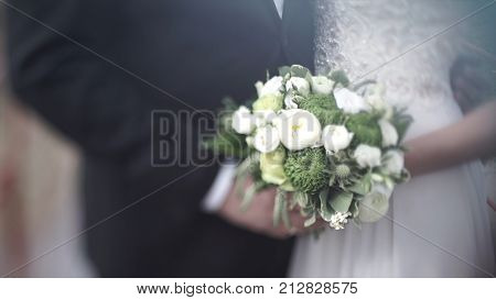 Bride and groom holding colourful wedding bouquet. Marriage concept. Beautiful young wedding couple outside in nature. Wedding couple with the stylish bouquet HD