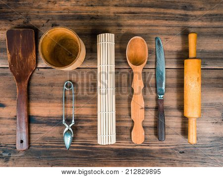 Wooden spoon, knife, rolling pin, turk for coffee, wooden mug and custard spoon for tea laid out on the table. Set of various kitchen tools on old wooden table, top view.