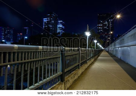 1st street bridge in Austin, TX crossing lady Bird Lake/ Hike and Bike Trail at night in downtown Austin, Texas with buildings in background