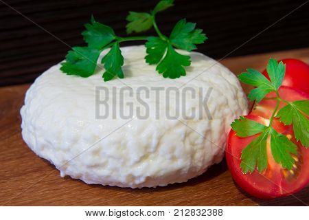Fresh cheese with excellent taste and aroma. Cheese on wooden cutting Board with tomatoes and fresh herbs.