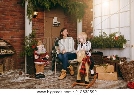 Young happy mother with a cute little child boy on rocking horse dressed in sweater in the decorated New Year room with Santa at home. Christmas good mood. Lifestyle family and holiday 2018 concept