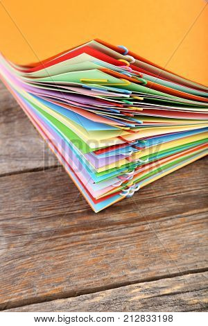 Stack Of Colored Papers With Paperclips On Wooden Table