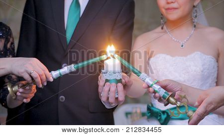 Light the candle. Two women light the big candle. Light the candle on a wedding. Wedding ceremony and tradition