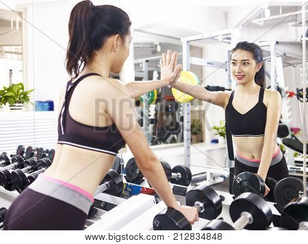 young asian woman looking at self in the mirror while exercising in fitness center focus on the mirror image.
