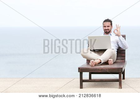 Businessman freelance on beach with laptop showing ok sign. Copy space for advertising