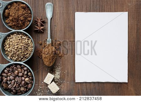 Coffee beans instant coffee and ground coffee in a metal measuring cup as well as sugar cubes a teaspoon star anise and white paper card are on dark wooden background with space for text; top view flat lay overhead view