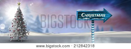 Digital composite of Christmas text on Wooden signpost in Christmas Winter landscape with Christmas tree