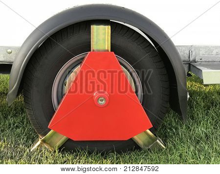 Red metal wheel clamp security device locked onto a trailer to prevent theft. On grass.