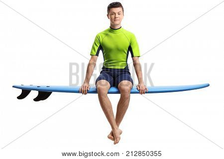 Teenage surfer seated on a surfboard isolated on white background