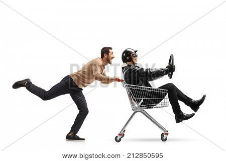 Young man pushing a shopping cart with a biker riding inside and holding a steering wheel isolated on white background