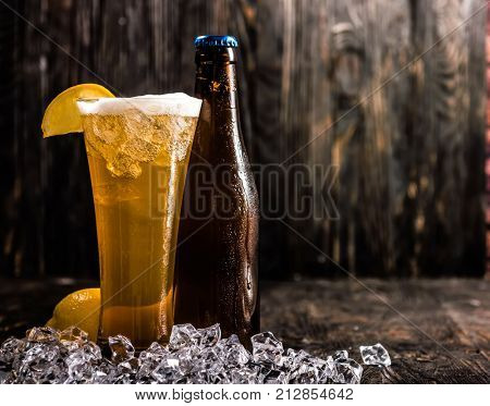 bottle and a glass of light beer with ice and lemon on dark wooden background