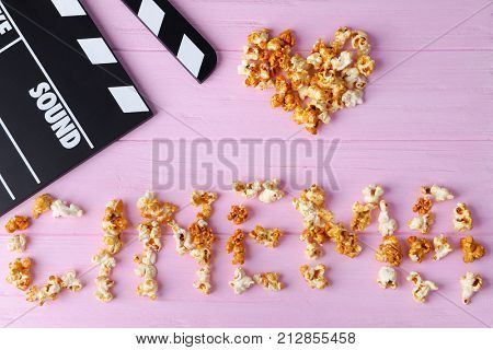 Movie clapper and word CINEMA made of caramel popcorn on color wooden background