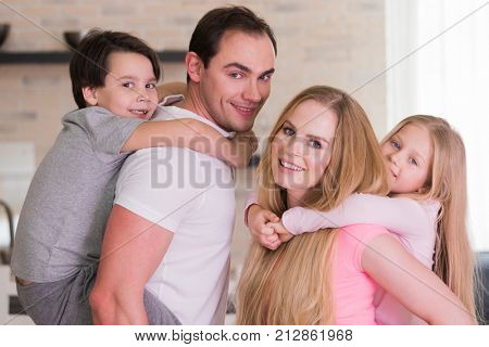 Portrait of happy family, father and mother giving boy and girl piggy back ride at home