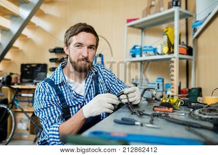 Self-employed repairman in gloves repairing chain from wheel of bicycle