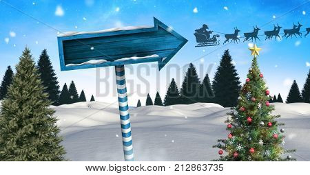 Digital composite of Wooden signpost in Christmas Winter landscape with Christmas tree and Santa's sleigh and reindeers