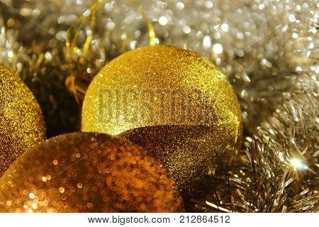 Christmas decorations. Golden balls and tinsel on the tree. Christmas toys. Gold jewelry with sequins. New year's tradition. To decorate the Christmas tree. Decorate the Christmas tree balls