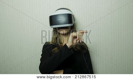 Woman using finger to touch on imaginary panel viewing on VR device against white wall. Girl use of vr device 4K