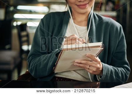 Close-up image of woman writing plans and ideas in textbook