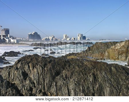 WINTER SEASCAPE, WITH HUGE BOULDERS IN THE FORE GROUND AND HIGH RISE BUILDINGS IN THE BACK GROUND 01fd