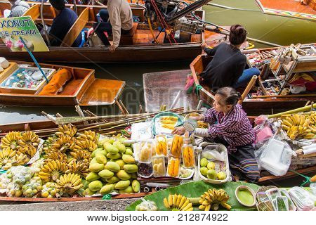 RATCHABURI THAILAND - NOVEMBER 5 : Local vendors selling goods at Damnoen Saduak Floating Market near Bangkok in Thailand on November 5 2017. Damnoen Saduak is a very popular tourist attraction.
