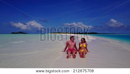 two 2 people together having fun man and woman together a romantic young couple sunbathing on a tropical island of white sand beach and blue sky and sea.
