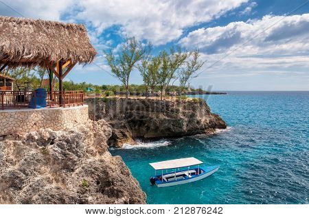 Caribbean rocky beach with turquoise water, tourists boat and lighthouse in Negril Jamaica.